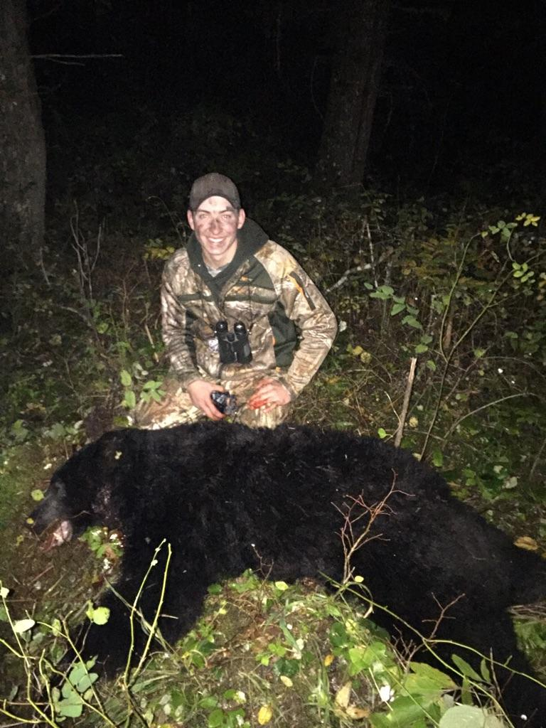 A man posing for the camera behind a black bear he harvested during a hunt with Bungalow Outfitters