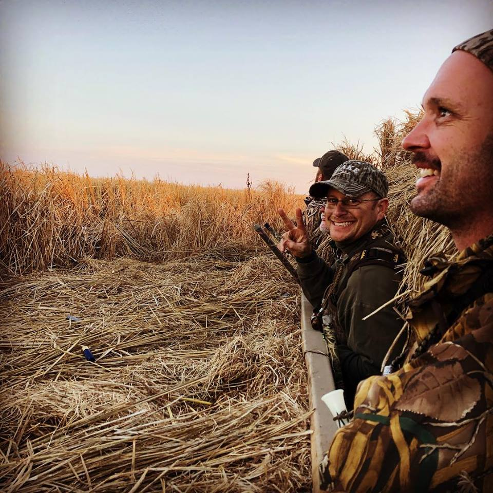 A group of men leaning out of a blind on a early morning with Fowl Lifestyle Outfitters