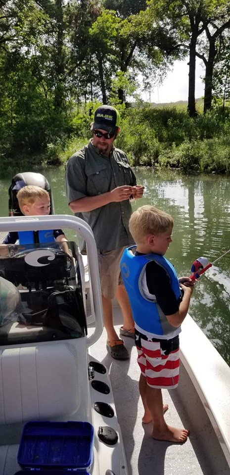A man and two little boys fishing off Bubba J's Guide Service's boat on Canyon Lake, TX