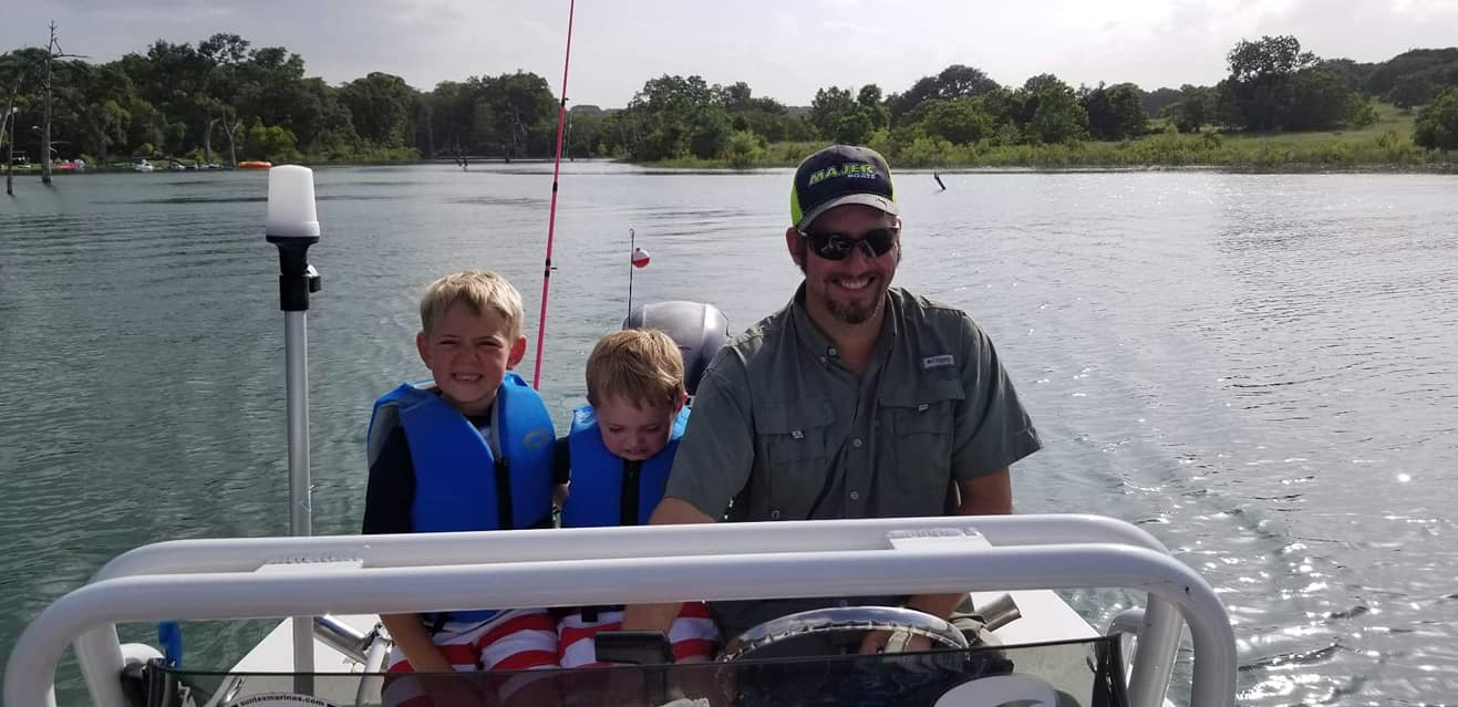 A father and his two boys driving a boat stocked with fishing gear
