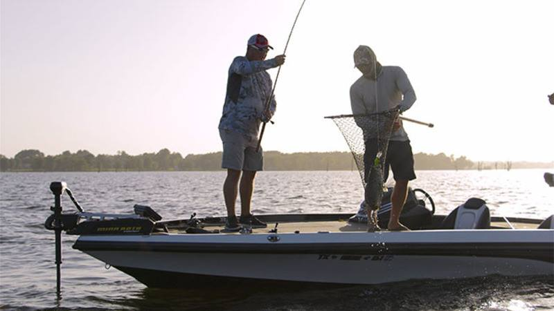 One man reeling in a fish while the other helps him land it in a fishing net on Lake Fork with Jason Hoffman's Lake Fork Guide Service