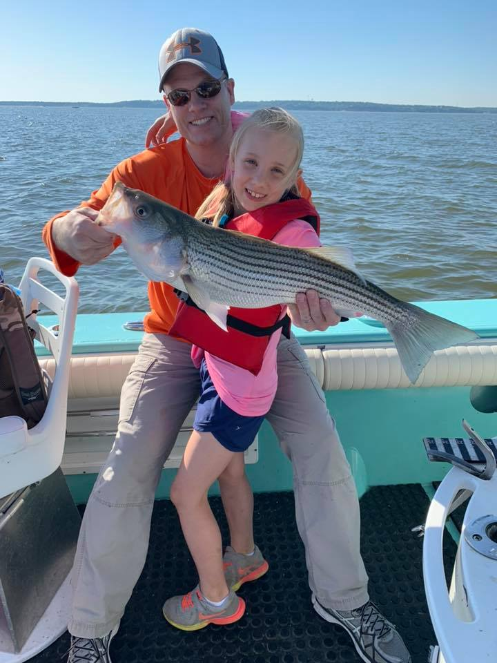 A father and daughter sitting on the edge of boat proudly displaying a large striper
