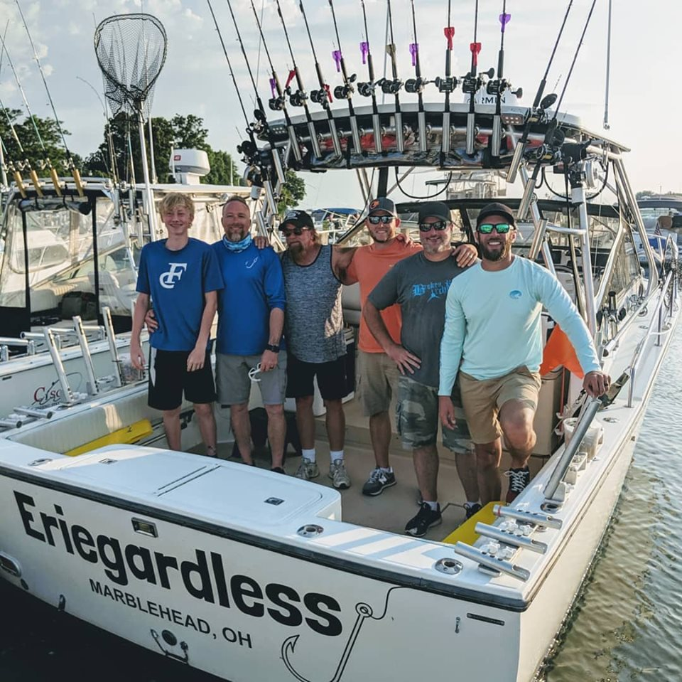 A group posing at the end of Eriegardless Sportfishing Charters boat while docked on Lake Erie