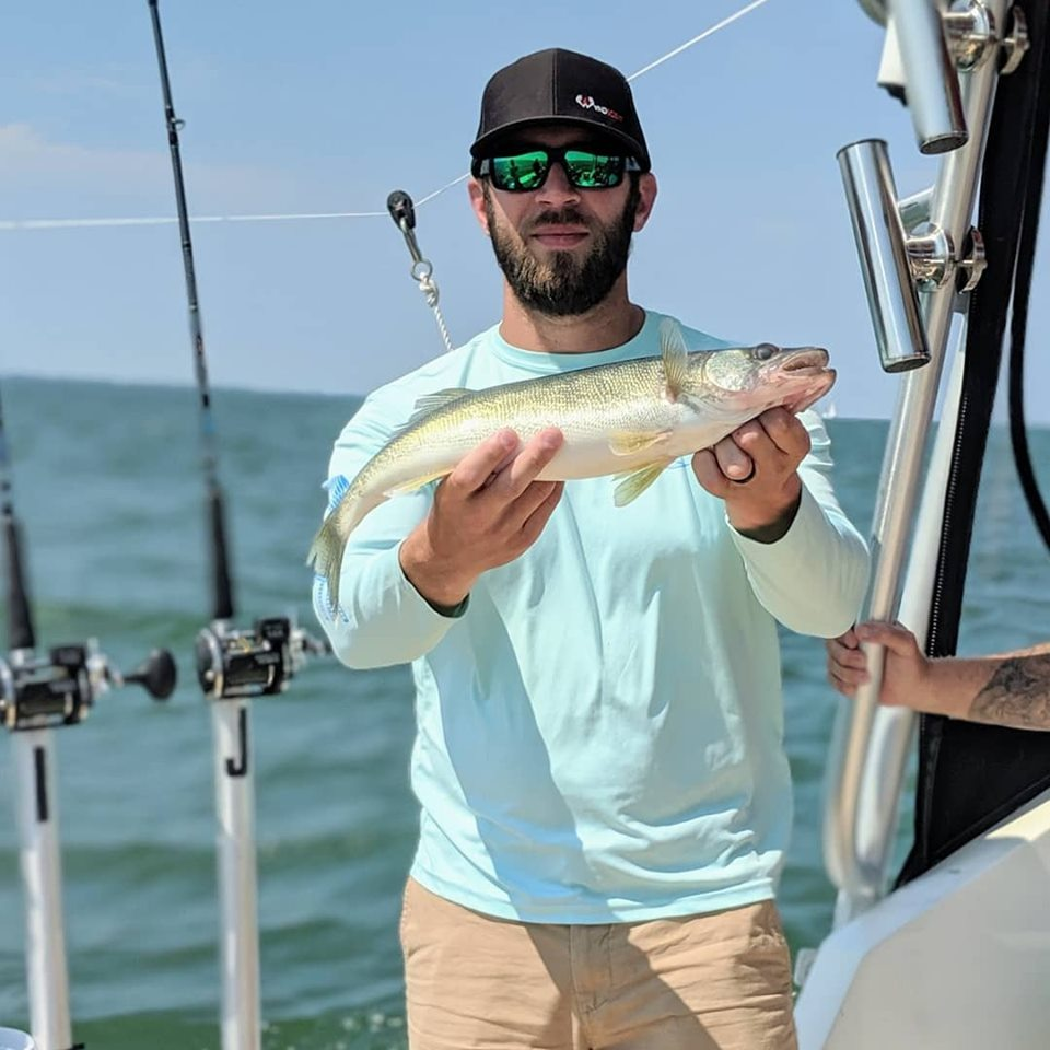 A man posing for the camera while holding a redfish on Eriegardless Sportfishing Charters boat