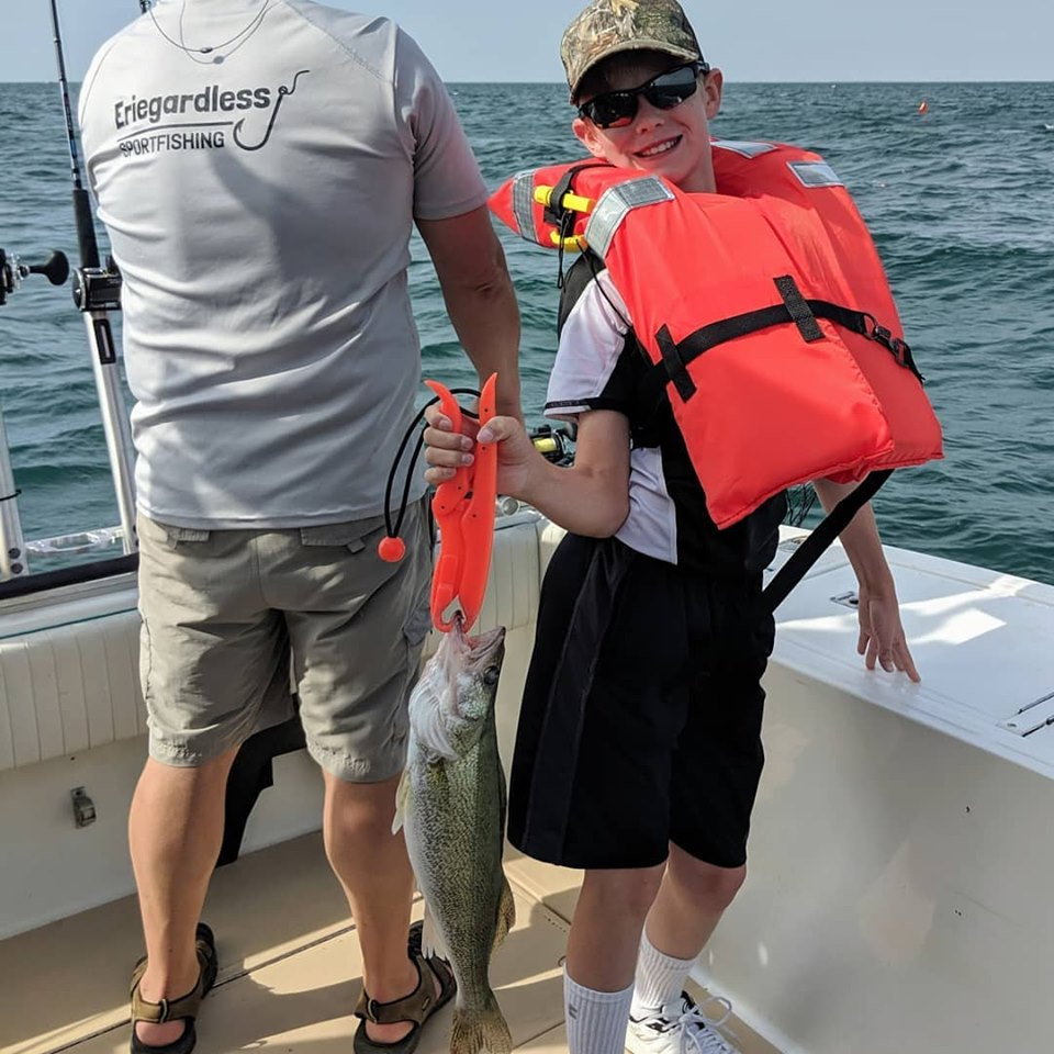 A young man wearing a orange life vest shows off his catch with Eriegardless Sportfishing Charters
