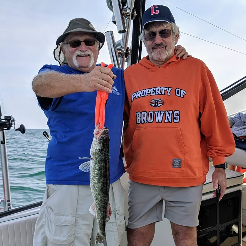 Two men show off their catch while fishing with Eriegardless Sportfishing Charters