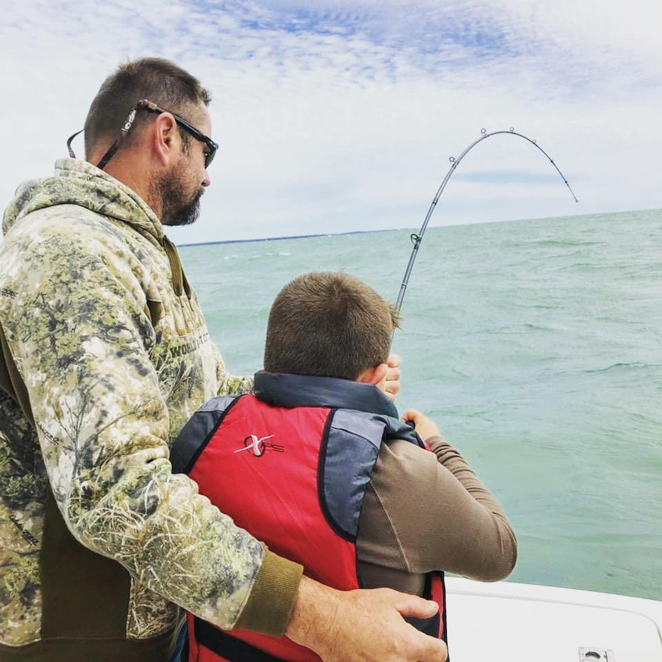 A father supports his son who is wearing a lifejacket as he reels in a fish into a boat