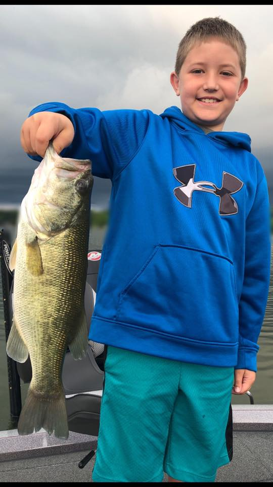 A young boy in a blue sweatshirt holding a bass by the lip