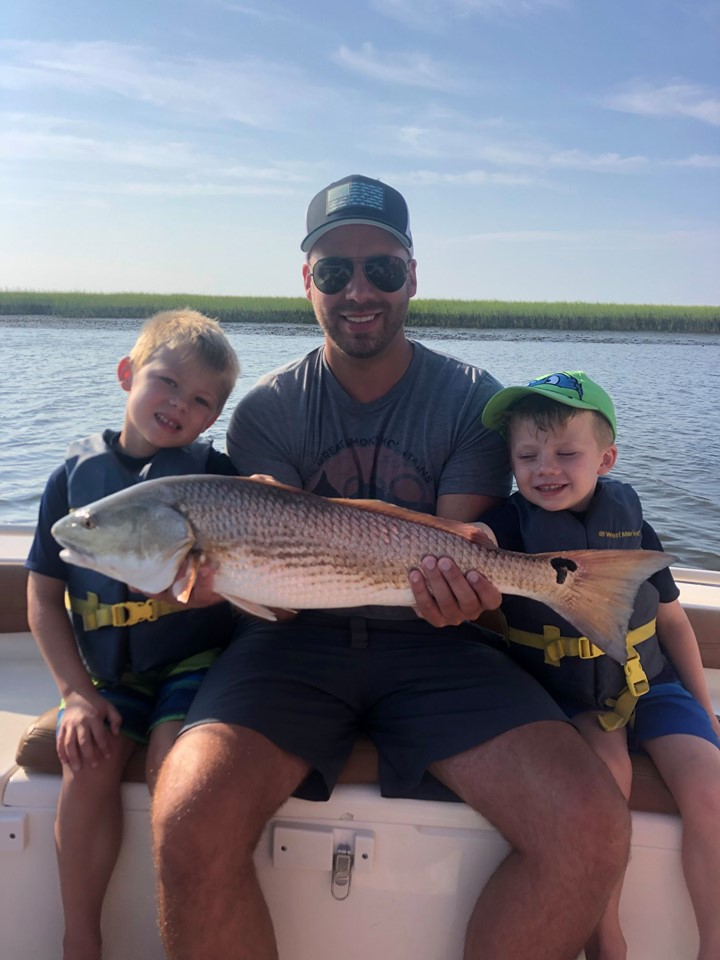 A father with his two sons sitting on either side of him on the back on boat holding a redfish