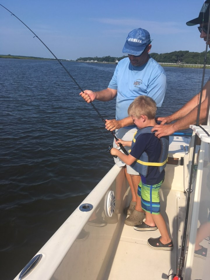 A young boy holding a fishing rod on a guided trip with North Mrytle Beach Fishing Charters