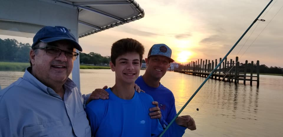 Three men smiling for the camera on Captain Smiley Fishing Charters boat with the sunsetting in the background