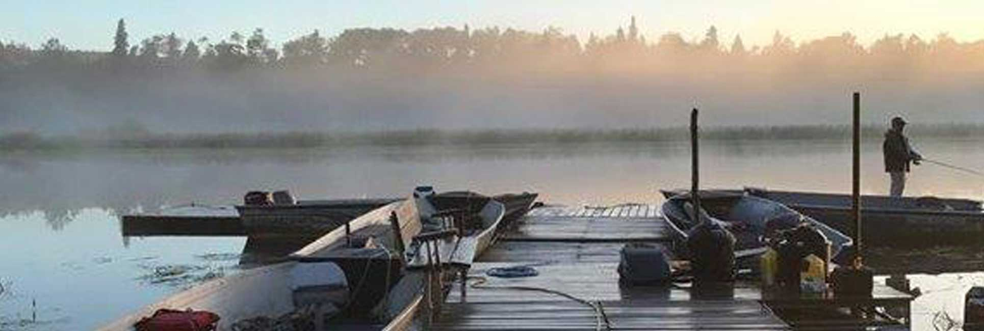 Wooden boat dock with two fishing boats on a foggy lake in Minnesota