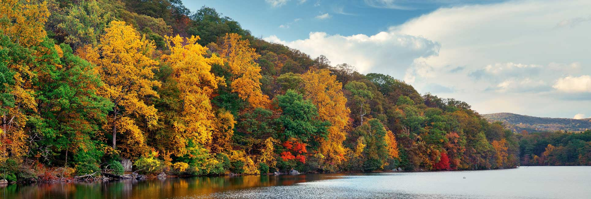 fishing lake in new york state with bright fall colored trees