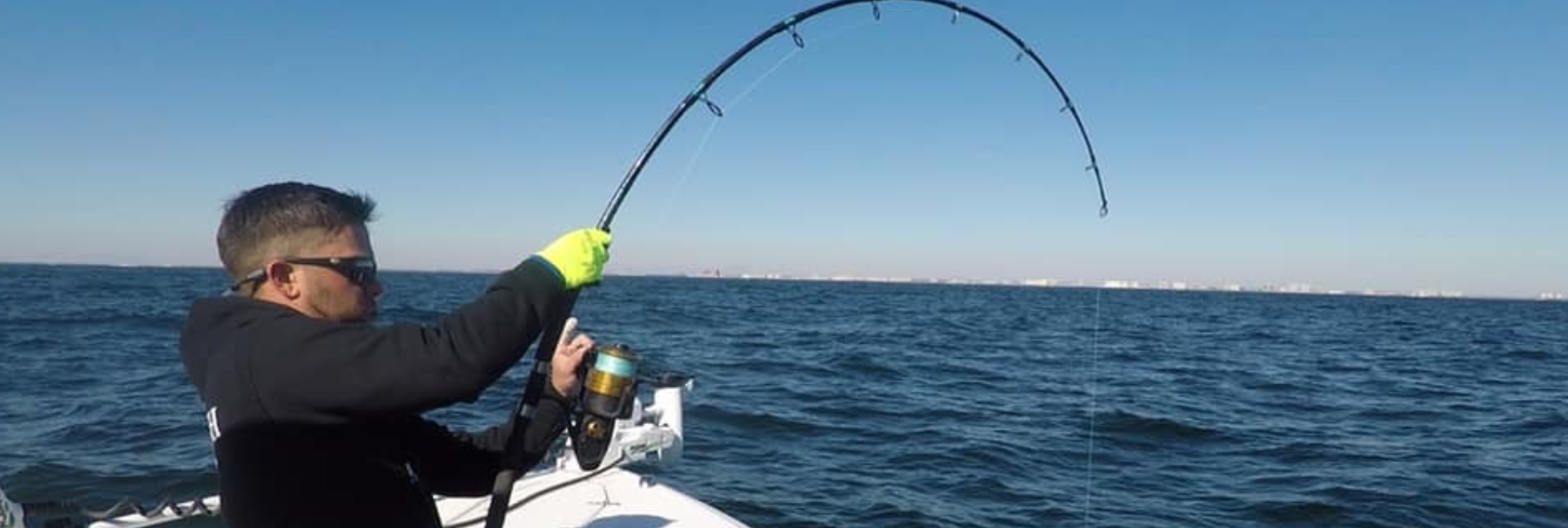 Florida fishing guide reeling in fish with a bent rod while deep sea fishing