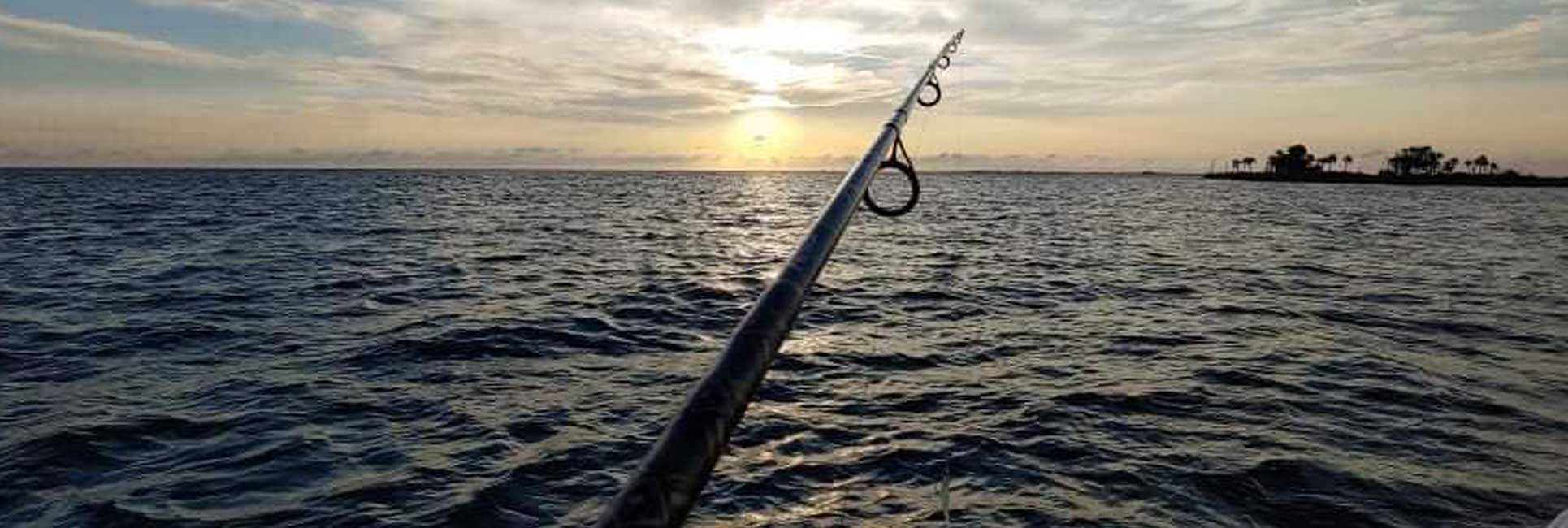 A fishing rod over the water with the sunsetting on Rodman Reservoir, FL.