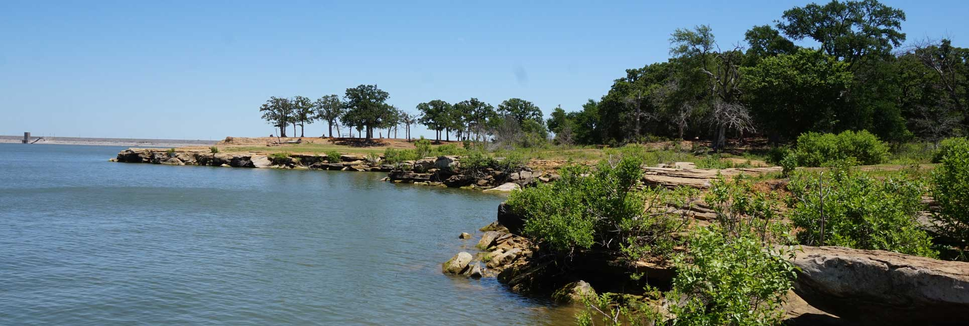 The small cliffs and rocks that line the shore of Grapevine Lake , Texas