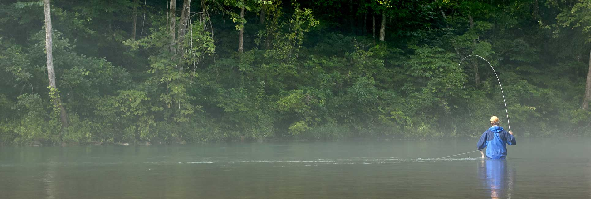 A man in blue fly fishing on a foggy morning in Missouri
