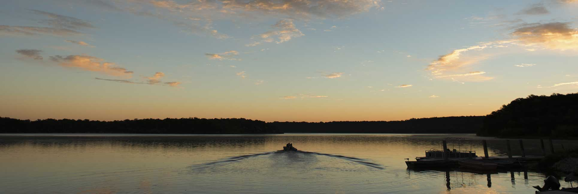 A bass boat leaving the dock with a small wake behind during sunrise on the clam waters of Lake Calaveras, TX