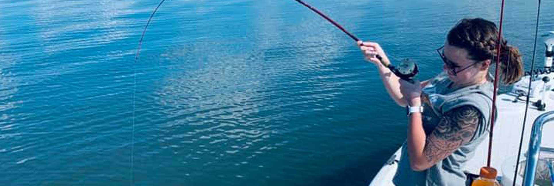 A women reeling in a fish with her rod bent on Lake Athens in Texas