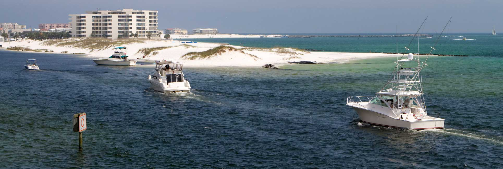 Fishing charter boats returning to the marina in between two sand bars in Destin, Florida.