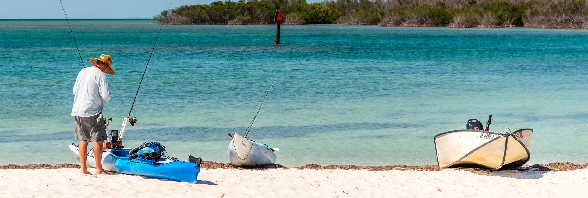 A man preparing for a chartered kayak fishing trip in key west Florida on the beach