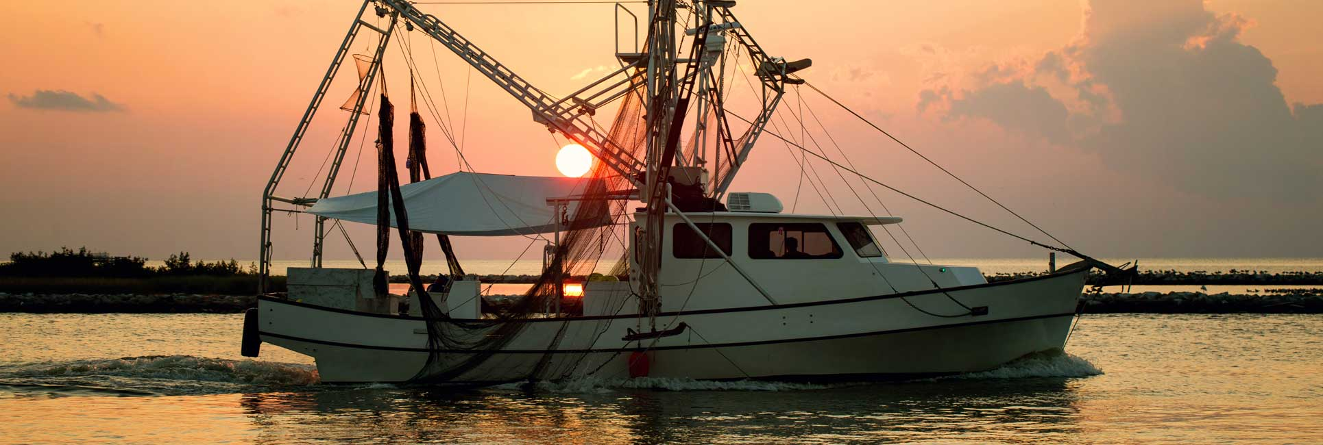A large fishing boat on the water in front of an orange sunset in Gulf Port, MS