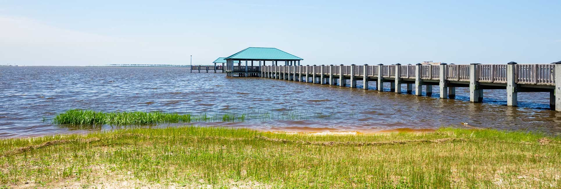A very long wooden pier with a roof at the end on the water in Ocean Springs, MS