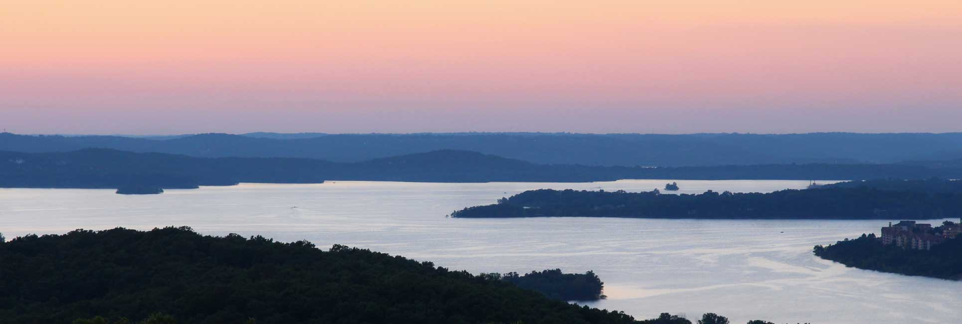 An aerial view of table rock Lake, MO surrounded by trees with the sunsetting in the distance