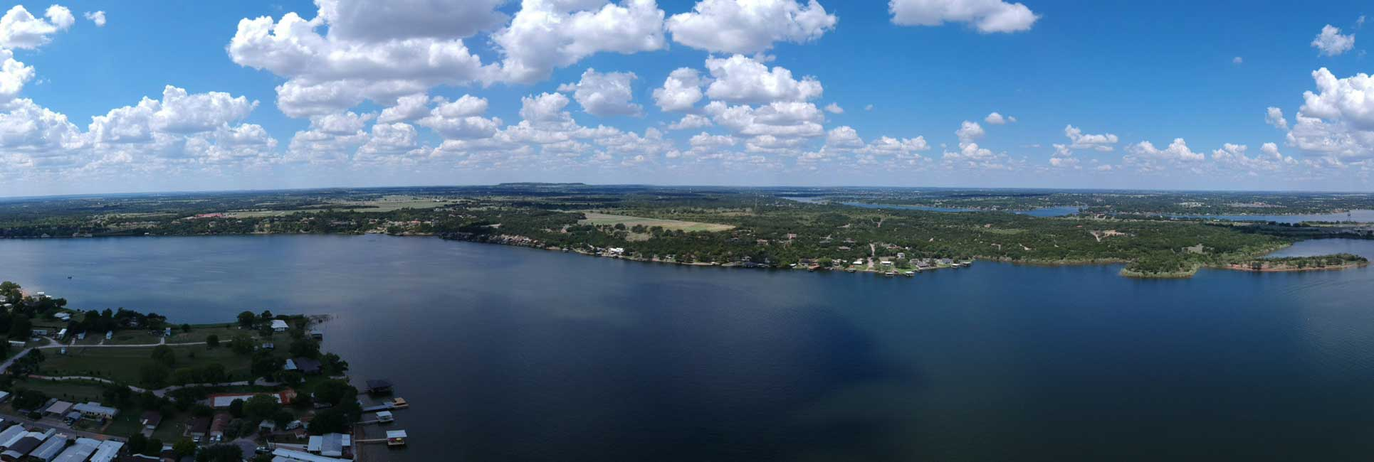 An aerial shot of Lake Granbury that includes docks, houses, fishing boats and blue water