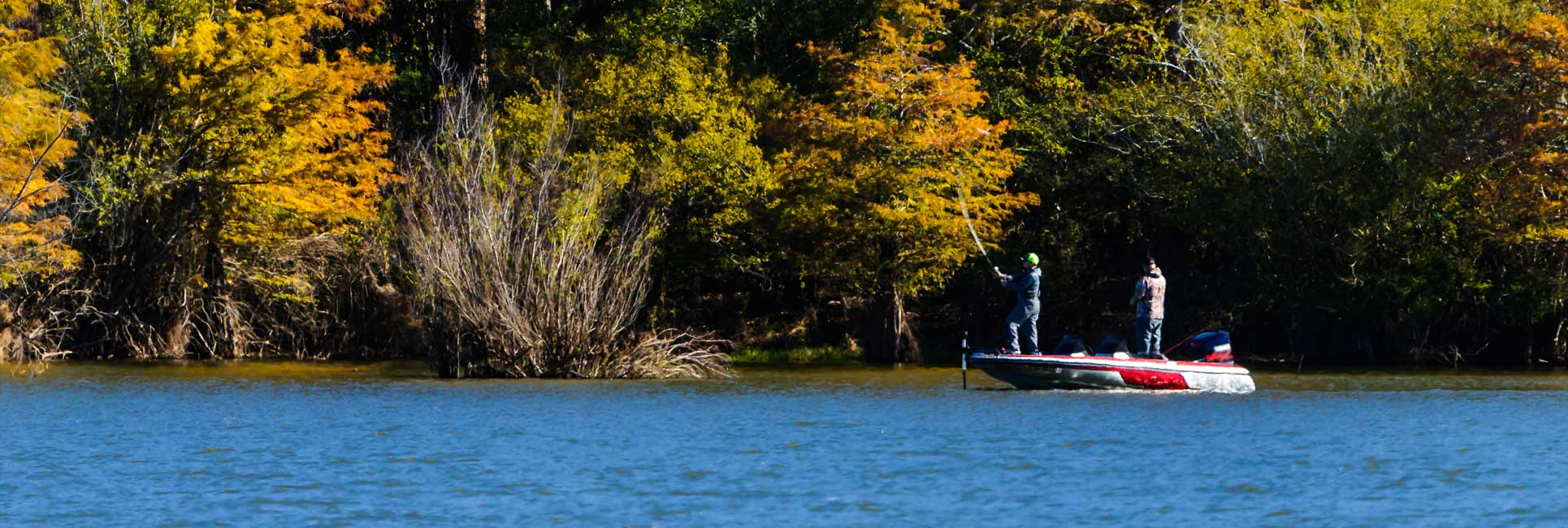 Two men fishing from a red and white bass boat on Lake Somerville, Texas