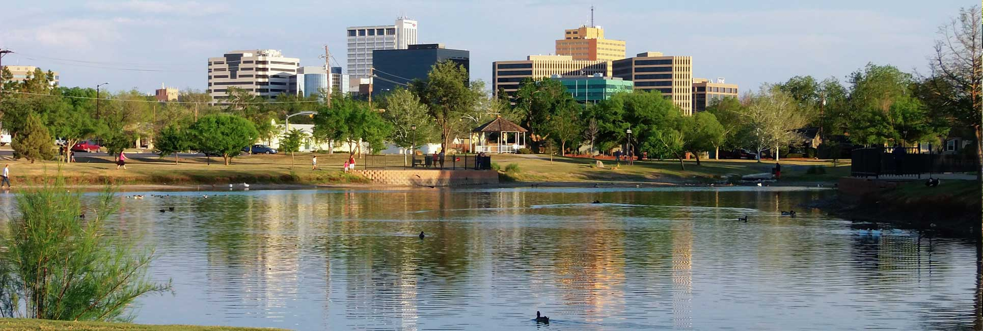 A view of downtown midland, TX over looking a lake where people are fishing and hiking.
