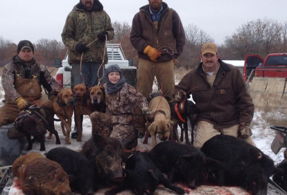 men with hogs and their dogs after hog hunting in oklahoma with bc fishing adventures