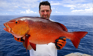 An angler holding a large snapper on a boat that he just caught with the ocean in the background